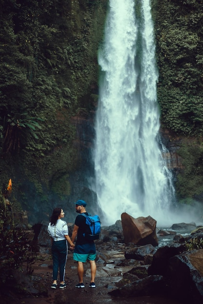 Young beautiful couple posing on the waterfall, travelers, hikers, backpacks Free Photo
