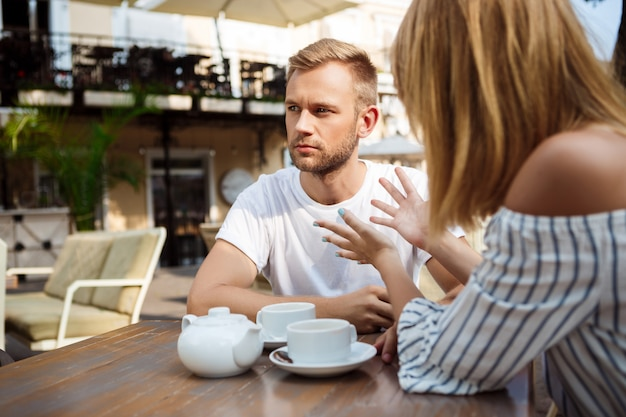 Young beautiful couple quarreling, sitting in cafe. Free Photo