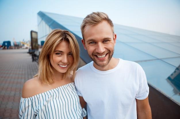 Молодая красивая пара, улыбаясь, обнимая, гуляя по городу Бесплатные Фотографии