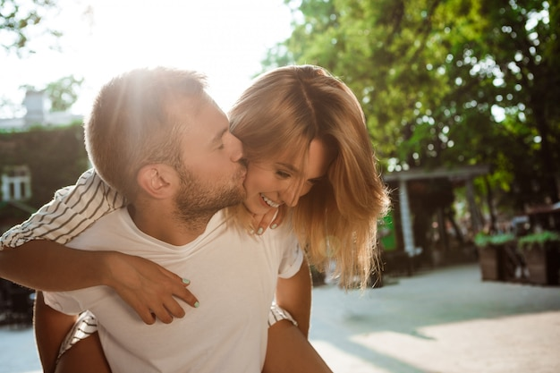 Young beautiful couple smiling, kissing, embracing, walking in park. Free Photo