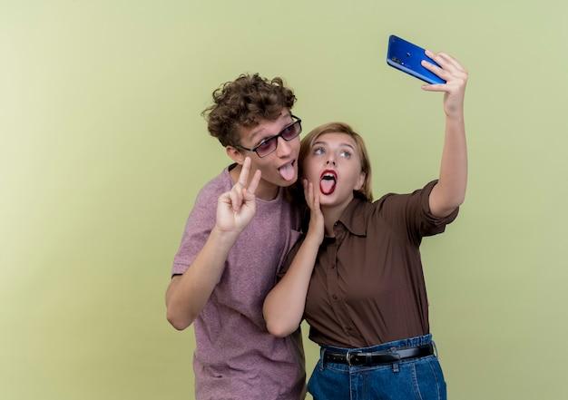 一緒に携帯電話を使用して若い美しいカップルは、舌を突き出して、光の上にvサインを見せて自分撮り笑顔を取ります 無料写真