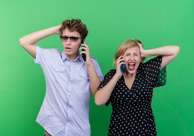 Giovane bella coppia uomo sconvolto e donna arrabbiata che parla sui telefoni cellulari in piedi sopra la parete verde Foto Gratuite
