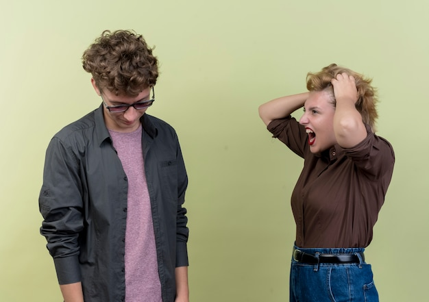 Young beautiful couple wearing casual clothes man and woman quarreling angry woman shouting at her boyfriend over light Free Photo