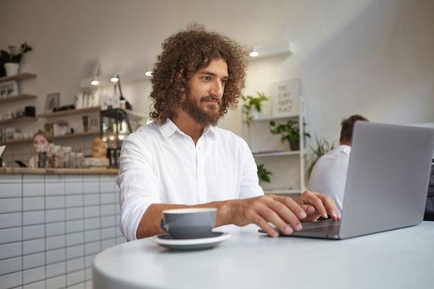 ノートパソコンとテーブルでコーヒーを飲みながらコーヒーショップに座って、白いシャツを着て、柔らかな笑顔で画面を見ている若い美しい巻き毛の男性フリーランサー 無料写真