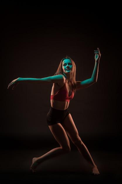 Young beautiful dancer in beige dress dancing on black Free Photo