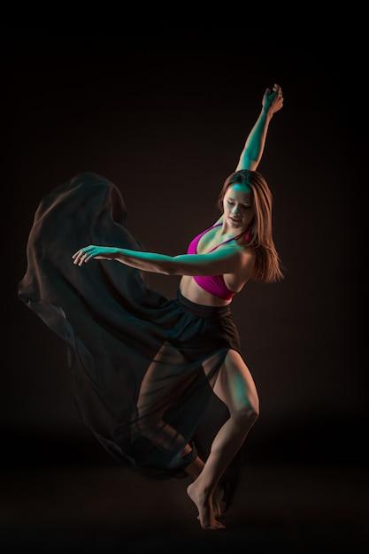 Молодая красивая танцовщица в бежевом платье танцует на черной стене Бесплатные Фотографии