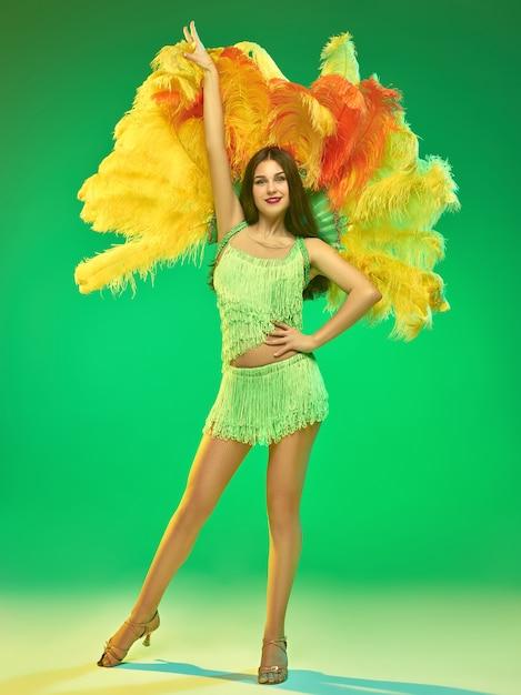 Young beautiful dancer posing on green wall Free Photo