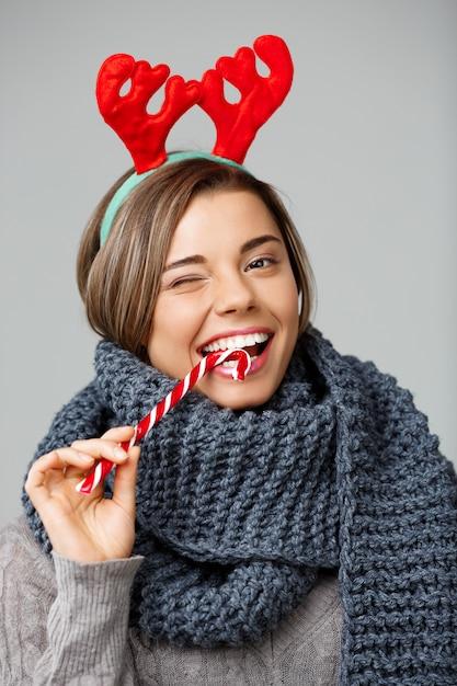 큰 뜨개질을 한 스카프와 크리스마스 순 록 뿔에 줄무늬 사탕을 먹고 웃 고 젊은 아름 다운 머리 불공평-여자. 무료 사진