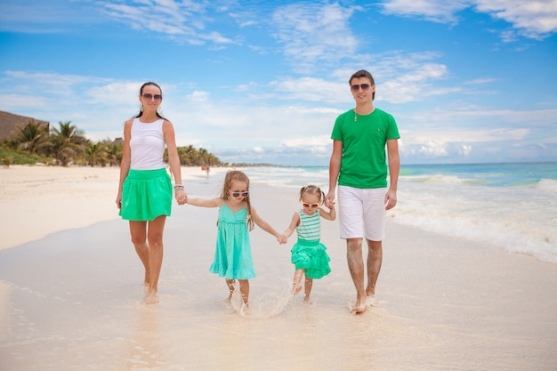 Young beautiful family of four enjoyed relaxing on the beach Premium Photo