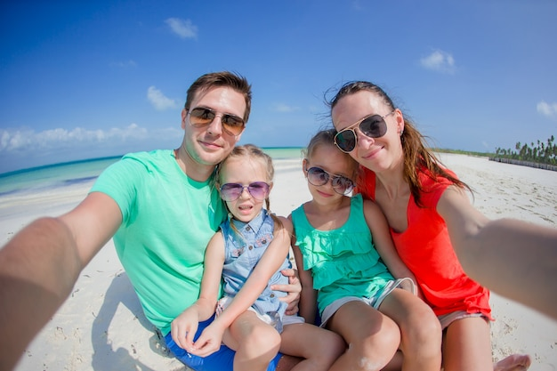 Young beautiful family taking selfie on the beach Premium Photo