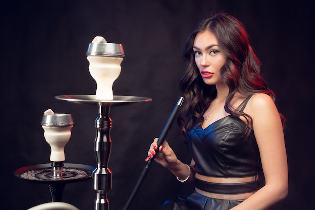 Young beautiful female in black dress smoking and exhales hookah Premium Photo