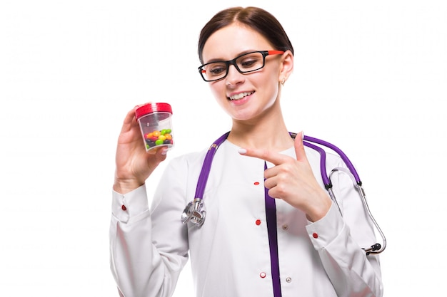 Young beautiful female doctor holding bottle of pills in her hands on white Premium Photo