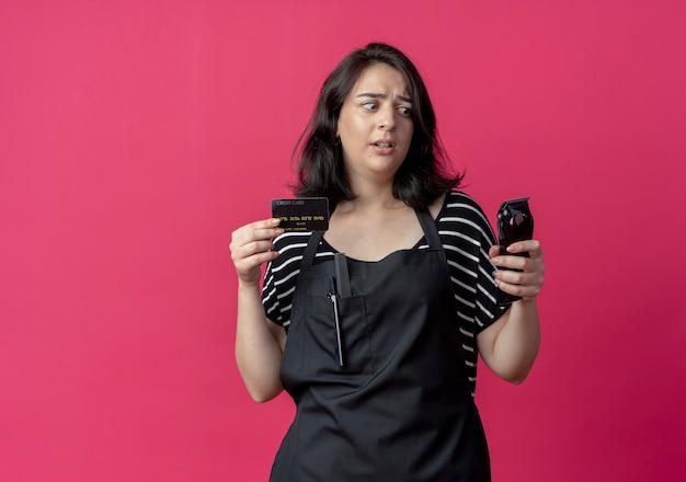 Giovane bella donna parrucchiere in grembiule che tiene macchina per il taglio dei capelli e carta di credito che sembra confusa e molto ansiosa sul rosa Foto Gratuite
