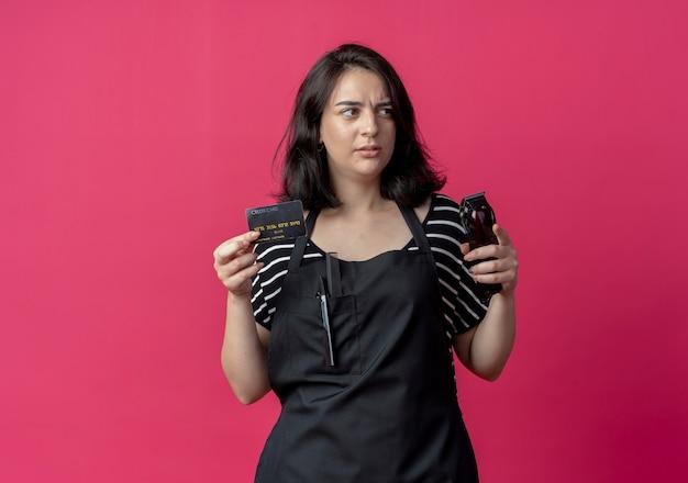 バリカンとクレジットカードを保持しているエプロンの若い美しい女性の美容師はピンクに戸惑いながら脇を見て 無料写真