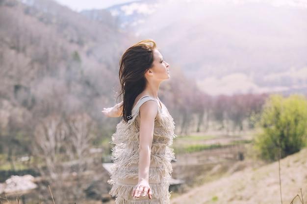 山と村、丘の上に立っている風景の中の若い美しい女性モデル Premium写真