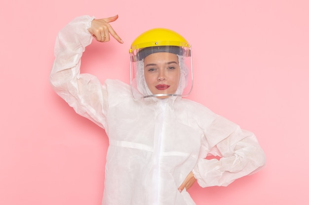 Young beautiful female in special white suit and yellow helmet posing on pink Free Photo
