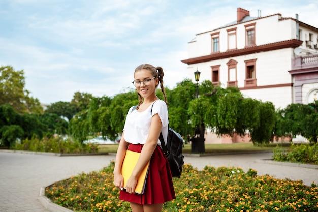 Молодая красивая студентка в очках, улыбаясь, держа папки на открытом воздухе, парк поверхности Бесплатные Фотографии