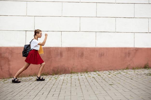 Молодая красивая студентка в очках шел по улице, держа папки Бесплатные Фотографии