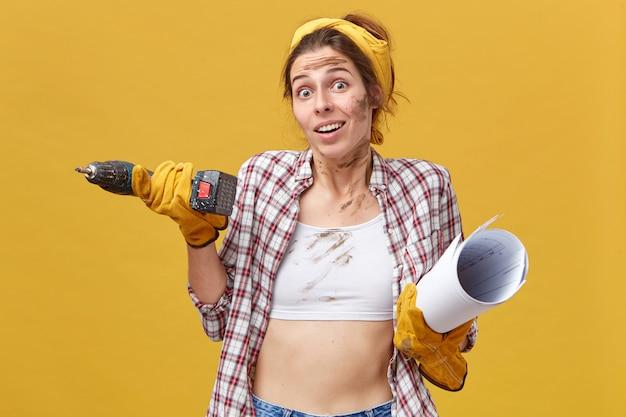 ドリルを保持している保守サービスの若い美しい女性労働者と青写真を身に着けているシャツと白いトップが彼女の肩をすくめて疑わしい顔をしています。人、職業、職業のコンセプトです。 無料写真