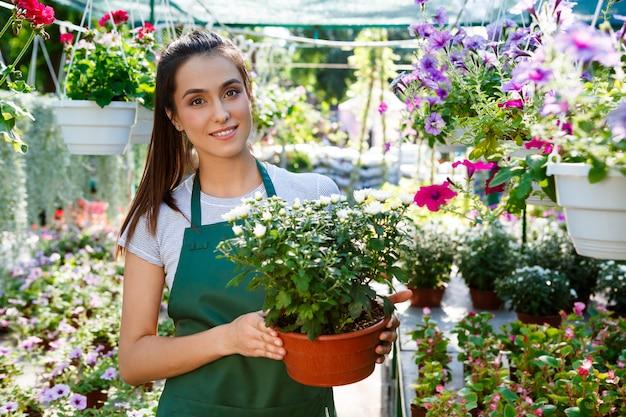 Young beautiful florist posing, smiling among flowers. Free Photo