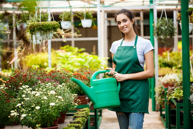 Young beautiful florist watering flowers. Free Photo