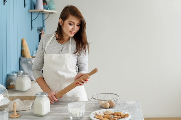 Young beautiful girl in an apron, making the dough cookies Premium Photo