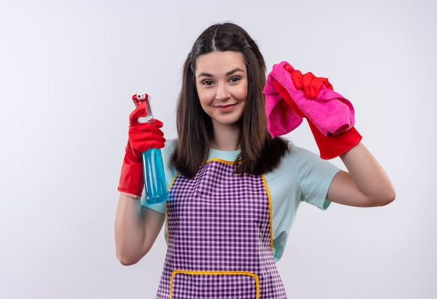 Young beautiful girl in apron and rubber gloves holding cleaning spray and rug looking at camera smiling cheerfully, ready for cleaning Free Photo