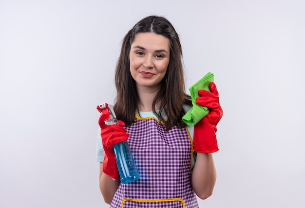 Young beautiful girl in apron and rubber gloves holding cleaning spray and rug smiling confident, ready for cleaning Free Photo