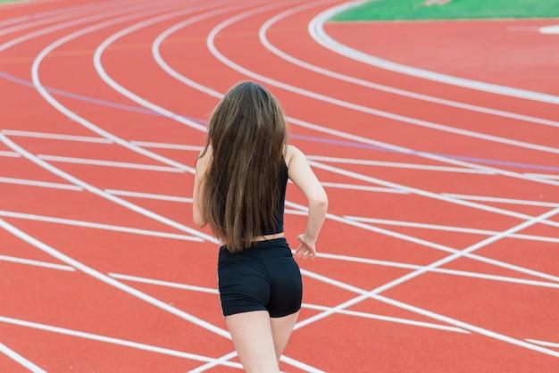 スポーツウェアの若い、美しい女の子のアスリートはトレーニングとランニング Premium写真