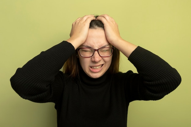 Giovane bella ragazza in un dolcevita nero e occhiali che si scatenano tenendosi per mano sulla sua testa Foto Gratuite