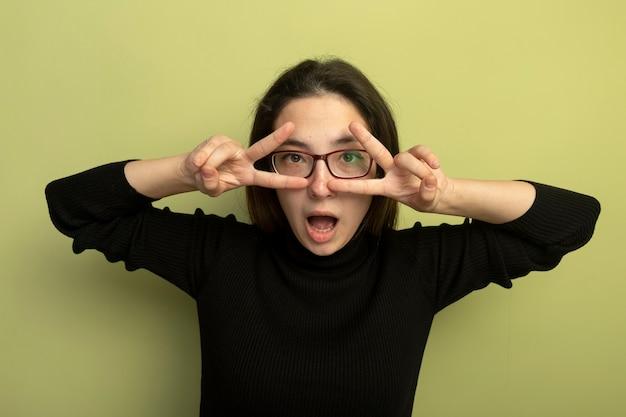 Giovane bella ragazza in un dolcevita nero e occhiali che fanno segno v con entrambe le mani guardando attraverso le dita Foto Gratuite