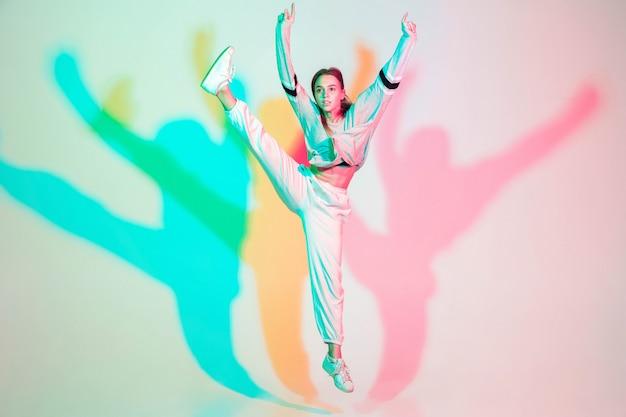Молодая красивая девушка танцует хип-хоп, уличный стиль, изолированные на студии Бесплатные Фотографии