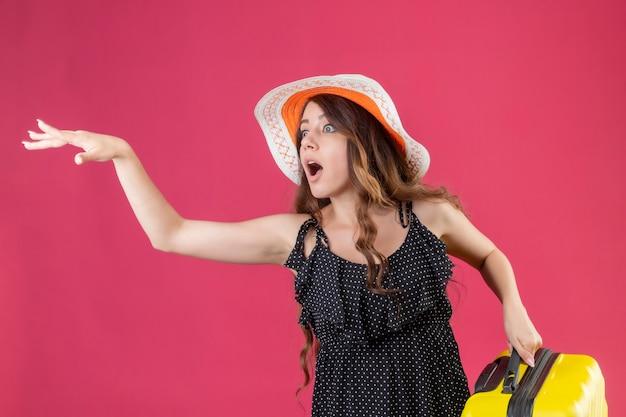 Giovane bella ragazza in abito a pois in cappello estivo che tiene la valigia essendo in ritardo chiedendo di aspettare agitando con la mano in piedi su sfondo rosa Foto Gratuite