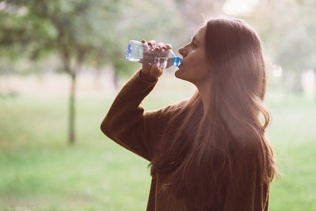 Young beautiful girl drinking water from plastic bottle on the street inpark in autumn or winter Premium Photo