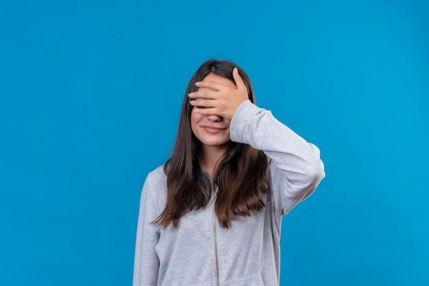 Giovane bella ragazza in felpa con cappuccio grigia con la mano sulla testa in piedi su sfondo blu Foto Gratuite