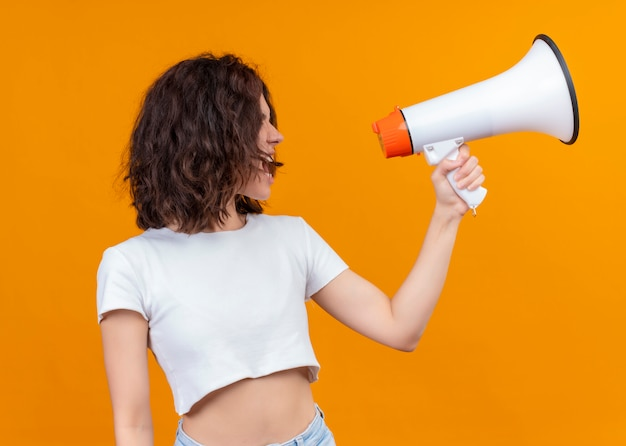 Young beautiful girl holding speaker and talking by it on isolated orange background Free Photo