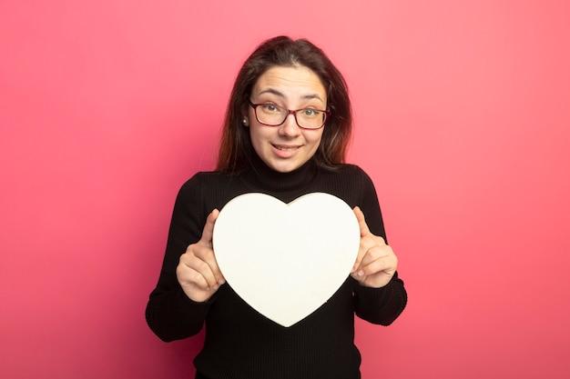 笑顔のハート型のボックスを保持している黒いタートルネックとメガネの若い美しい少女 無料写真