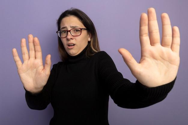 Молодая красивая девушка в черной водолазке и очках делает стоп-жест, протягивая открытую руку, будучи напуганной Бесплатные Фотографии