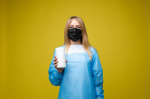 使い捨て医療用ガウンと彼女の顔にマスクを持つ若い美しい少女は、黄色の背景で隔離の肖像画、濡れた抗菌ワイプを保持 無料写真