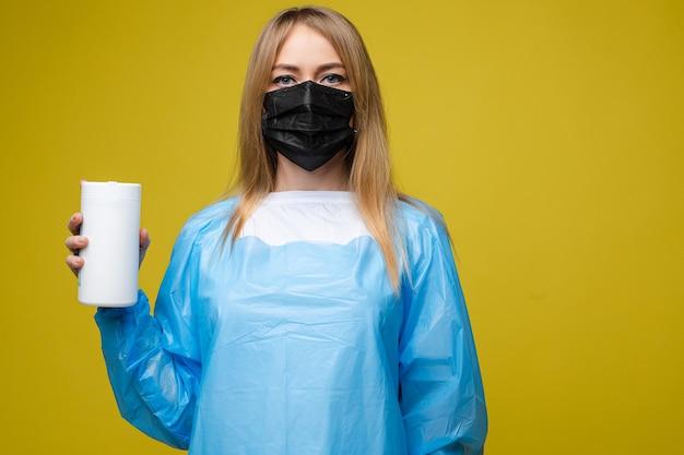 Молодая красивая девушка в одноразовом медицинском халате и с маской на лице держит влажные антибактериальные салфетки, портрет изолирован на желтом фоне Бесплатные Фотографии