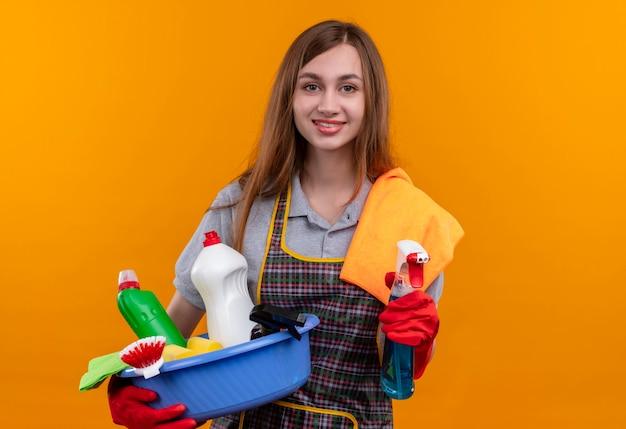 エプロンとゴム手袋で洗面器を保持している若い美しい少女は、幸せで前向きな笑顔の敷物とスプレー 無料写真