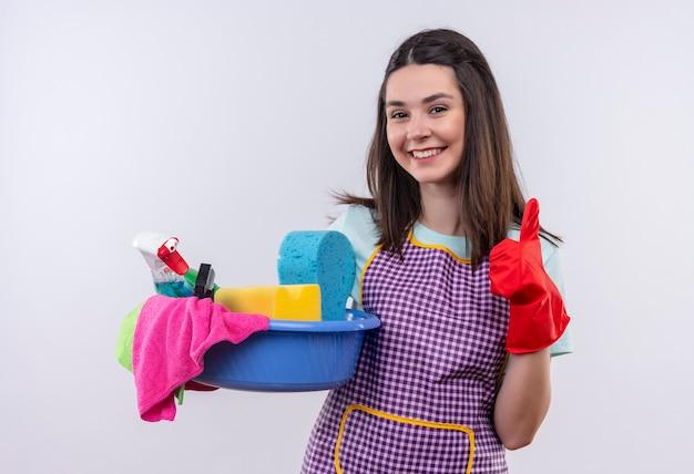 엄지 손가락을 보여주는 행복 한 얼굴로 웃 고 청소 도구와 분지를 들고 앞치마와 고무 장갑에 젊은 아름 다운 소녀 무료 사진