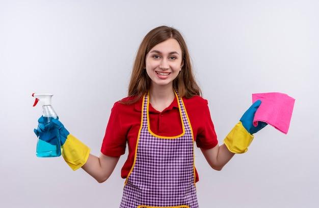 エプロンとゴム手袋の若い美しい少女は、元気に笑顔でカメラを見ているクリーニングスプレーと敷物を保持し、wjiteの背景を掃除する準備ができています 無料写真