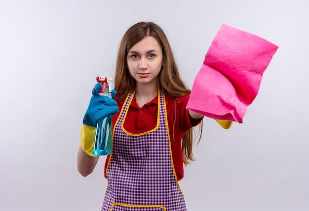 エプロンとゴム手袋で若い美しい少女が掃除スプレーと敷物を持ってカメラの笑顔を見て、掃除の準備ができて 無料写真