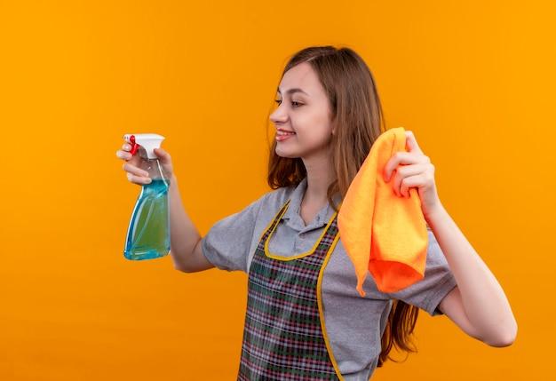 笑顔を脇に見て、掃除の準備ができて、掃除スプレーと敷物を保持しているエプロンの若い美しい少女 無料写真
