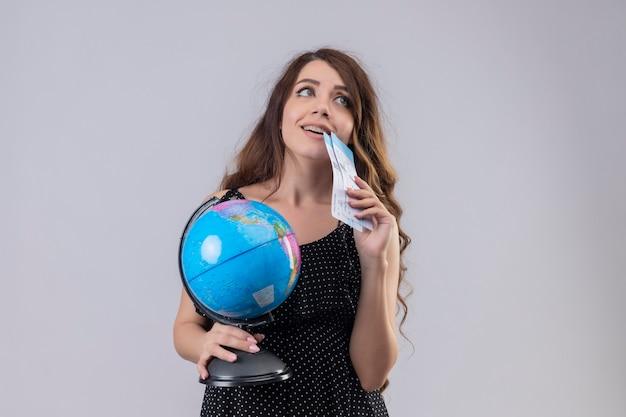 Молодая красивая девушка в платье в горошек, держащая авиабилеты и глобус, глядя вверх стоя с мечтательным взглядом на белом фоне Бесплатные Фотографии