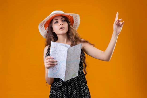 Молодая красивая девушка в платье в горошек в летней шляпе держит карту, жестикулируя, подождите минуту с серьезным уверенным выражением лица, стоящим на желтом фоне Бесплатные Фотографии