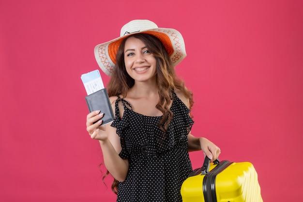 분홍색 배경 위에 유쾌하게 미소를 카메라를보고 항공 티켓을 들고 가방으로 서 여름 모자에 폴카 도트 드레스에서 젊은 아름 다운 소녀 무료 사진