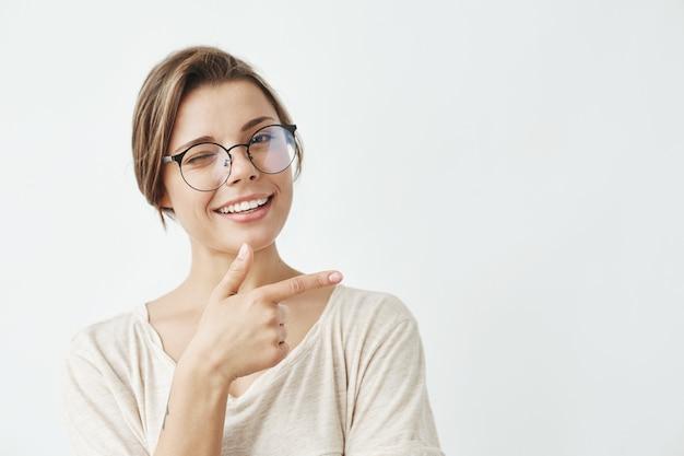 Молодая красивая девушка в очках, улыбаясь, подмигивая указательным пальцем в сторону. Бесплатные Фотографии