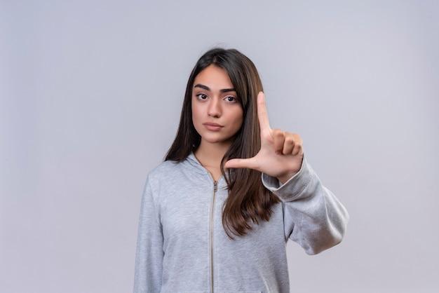 Молодая красивая девушка в серой толстовке с капюшоном показывает знак небольшого размера с серьезным символом меры лица, стоящим на белом фоне Бесплатные Фотографии